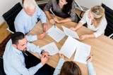 51756055 - lawyers having team meeting in law firm reading documents and negotiating agreements