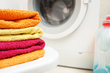 washed towels stacked with washing machine in background