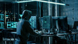 Hooded Hacker Using His Comuter with Different Information to Break into Corporate Data Servers and Infects them with Virus. His Hideout Place has Dark Atmosphere, Multiple Displays, Cables Everywhere.
