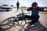 Bicyclists injured in a car accident lying down on the road and holding his head with helmet. A person who is driving car running to helps to injured man