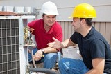 Air conditioning repairmen discussing the problem with a compressor unit.