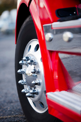 The powerful front wheel on the steering axle of the truck on a powerful modern aluminum wheels with chrome mounting bolts. Detail of a red truck with a wing and chrome complements the steps of the magnitude of this giant.