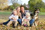 A happy family of four people, including mother, father, young child, and toddler brother are sitting outside in the fallen maple leaves with their pet German Shepherd dog on an Autumn day.
