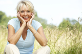 Portrait of mature woman sitting in countryside smiling